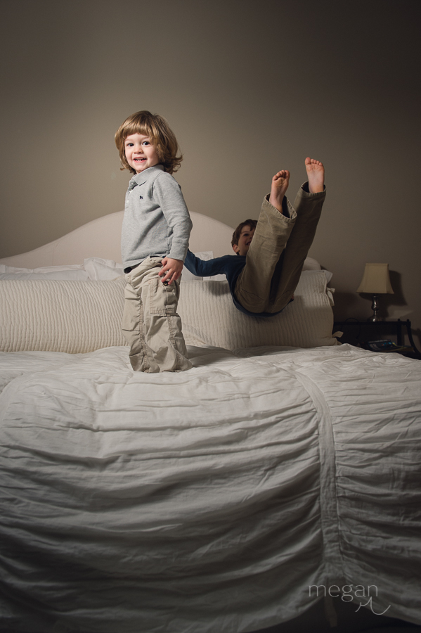 children jump on a large bed lit with off camera flash