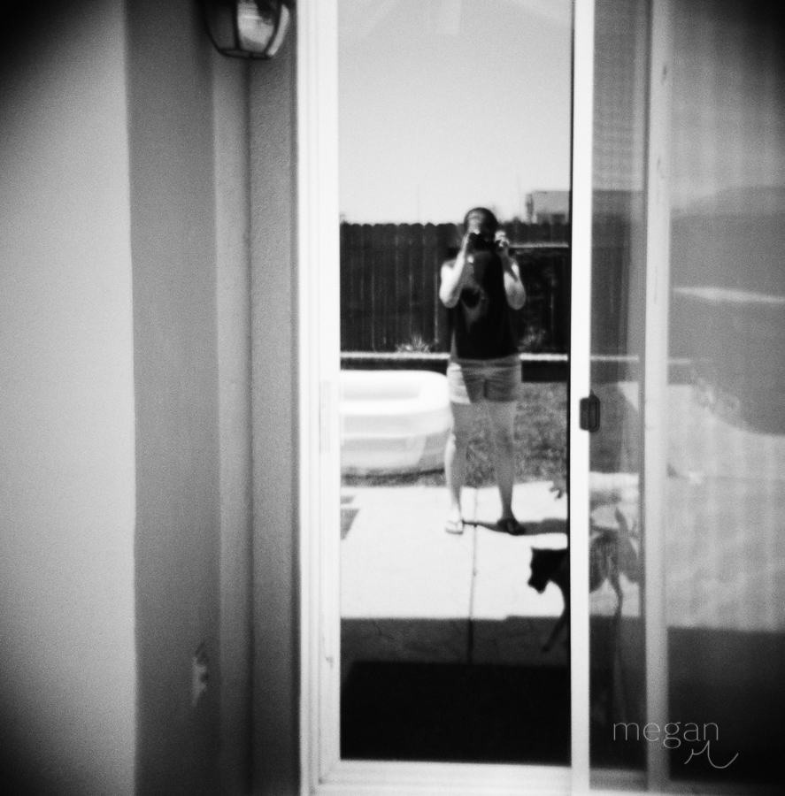 Photographer reflected in sliding glass door in Black and white film image