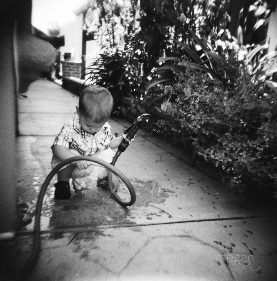 Toddler plays with hose outside in black and white on film