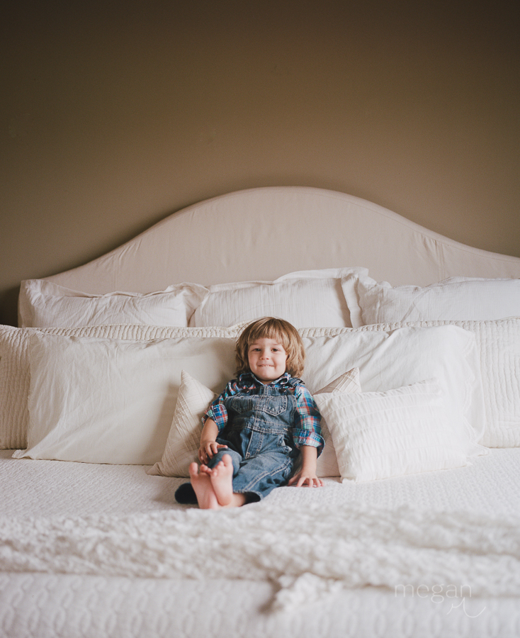 portrait of toddler on white bed shot with portra 400 in natural light