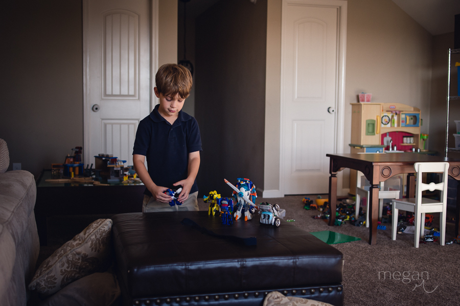 A boy plays with transformer toys in a playroom