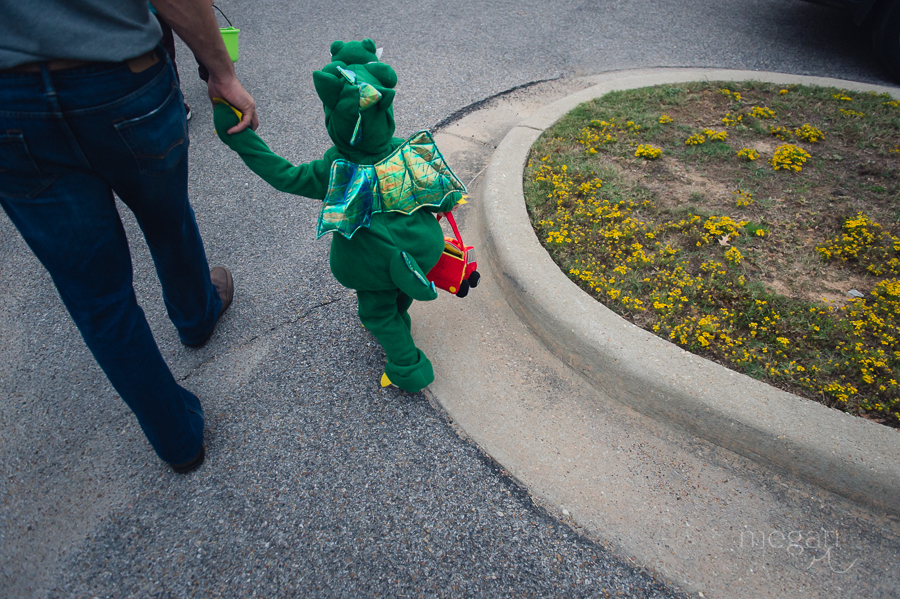 man holds hand with toddler dressed up as a dragon