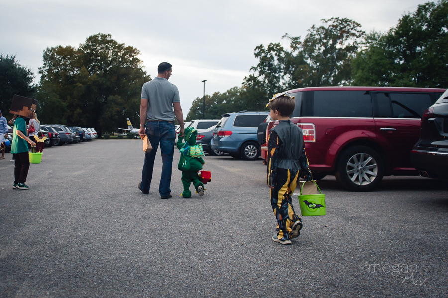 Man and children in holiday costumes walk through a parking lot.