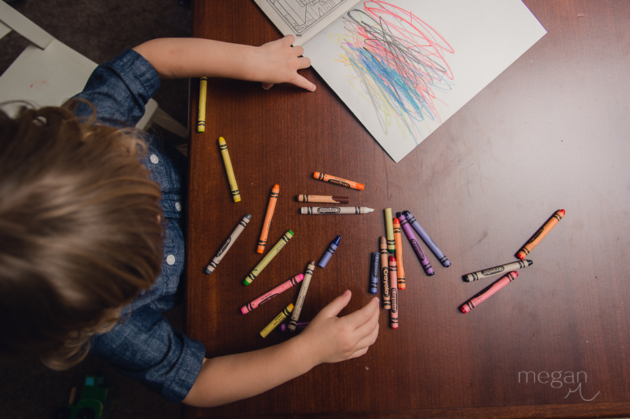 Toddler scribbles in coloring book amongst many crayons