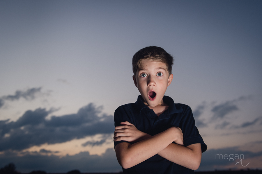 Boy in front of sunset sky with clouds