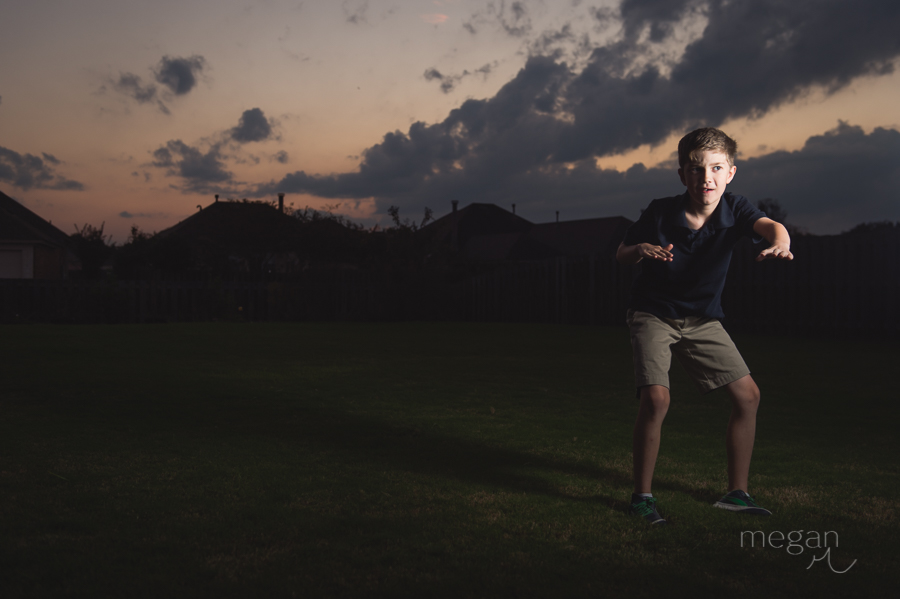 boy strikes a pose in front of sunset with clouds