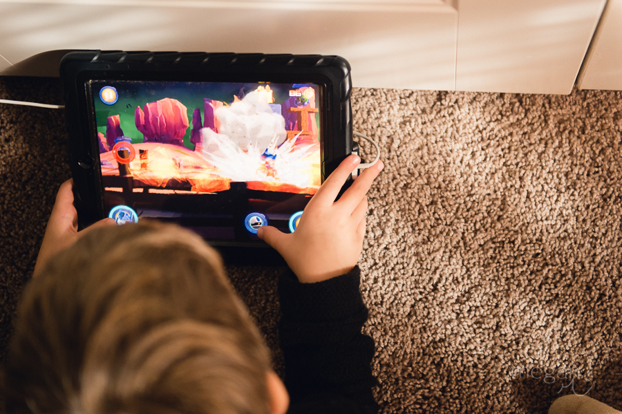 young boy plays a game on an iPad in natural light