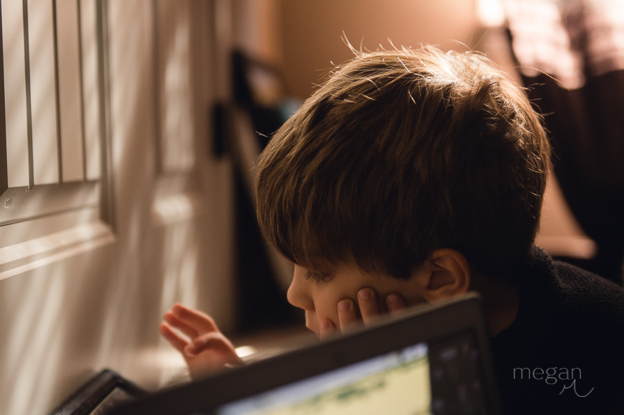 picture of young boy playing on an iPad in natural light