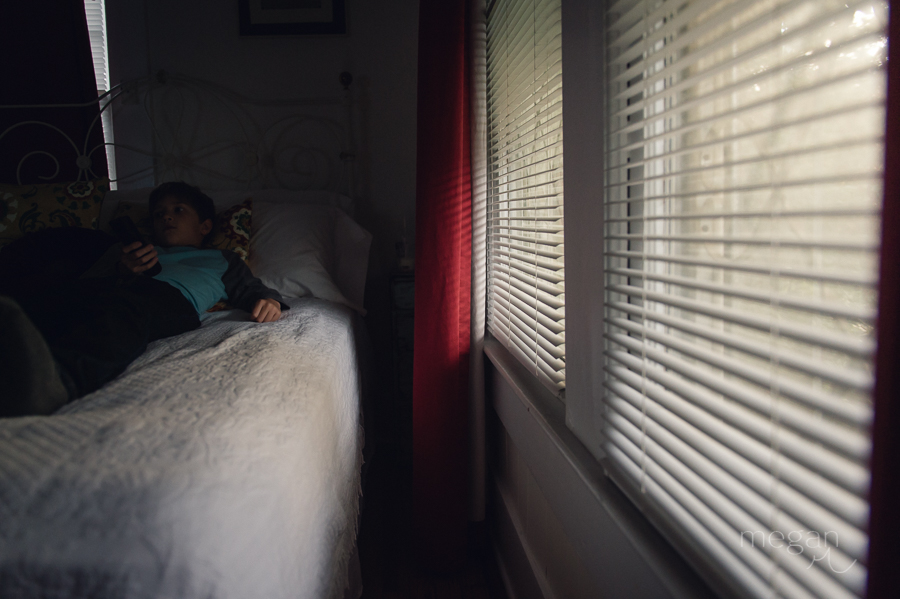 boy rests on bed in late afternoon natural light