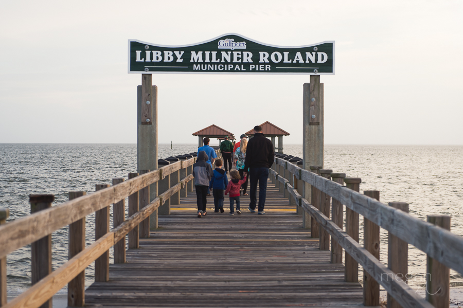 people walk down libby milner roland pier in gulfport mississippi at sunset