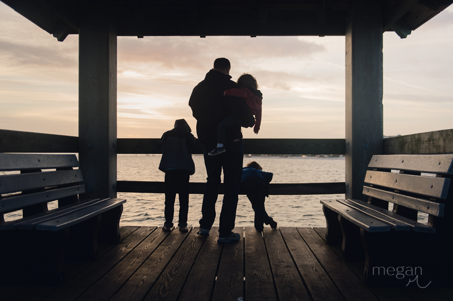 family in silhouette on pier during sunset in gulfport mississippi
