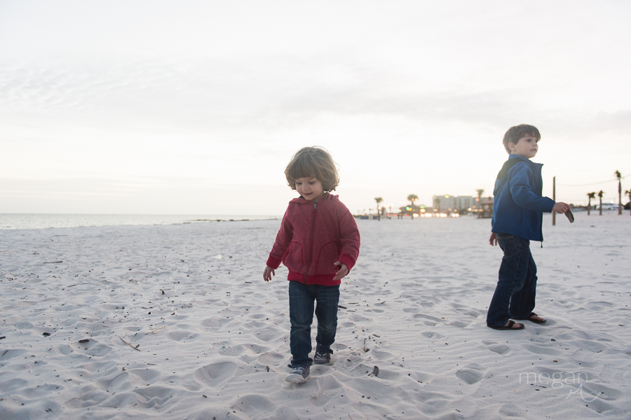 Toddler plays on the beach at sunset
