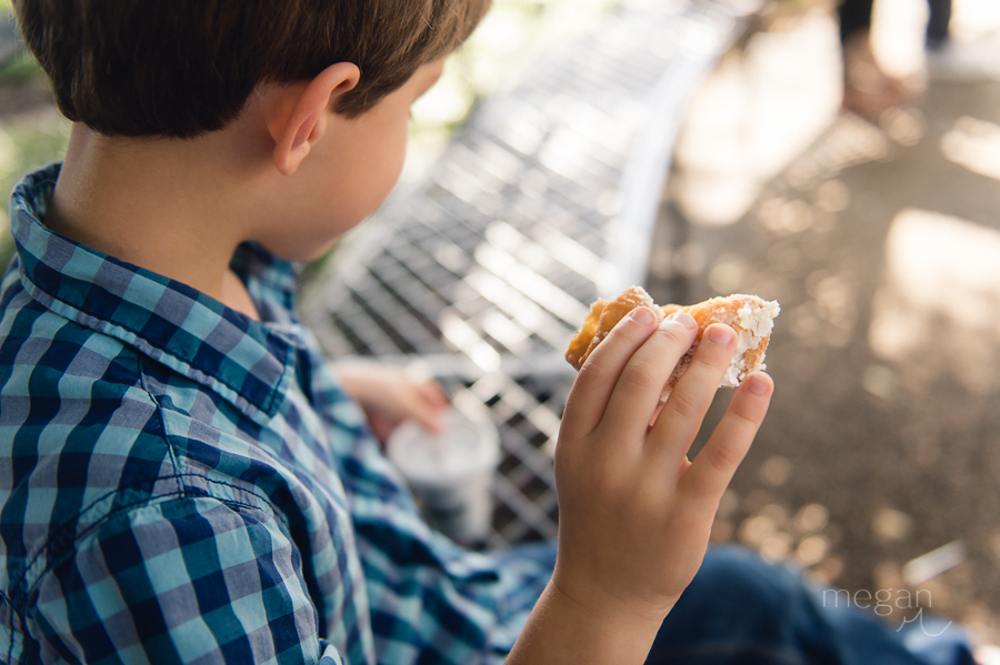 young boy with beignet and hot chocolate on park bench