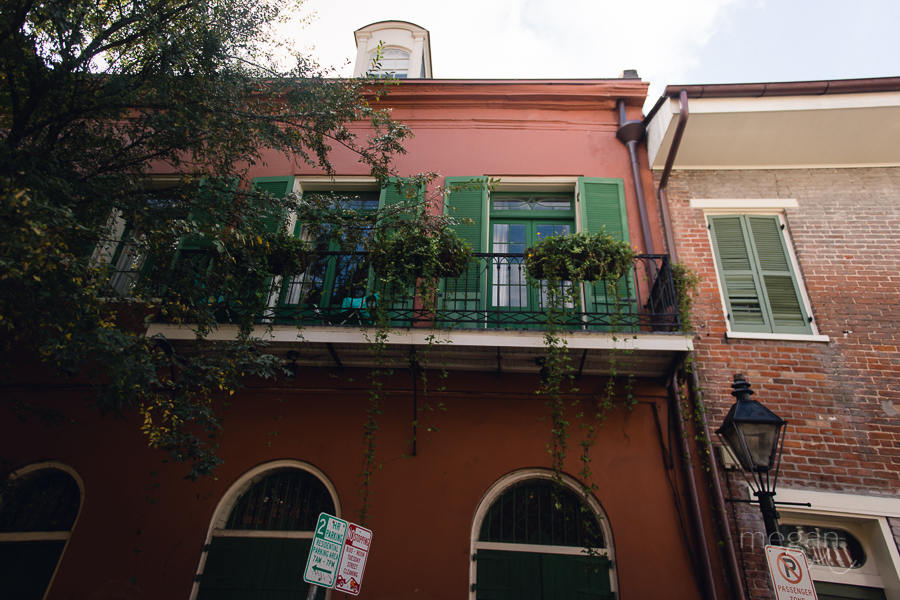 wrought iron balcony on pink building in the french quarter of new orleans