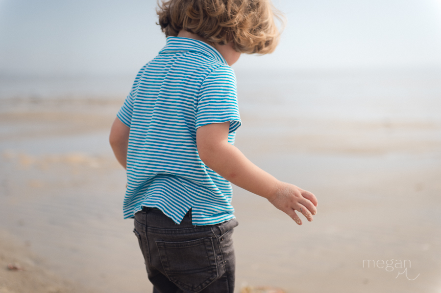 toddler walks on sand at the beach