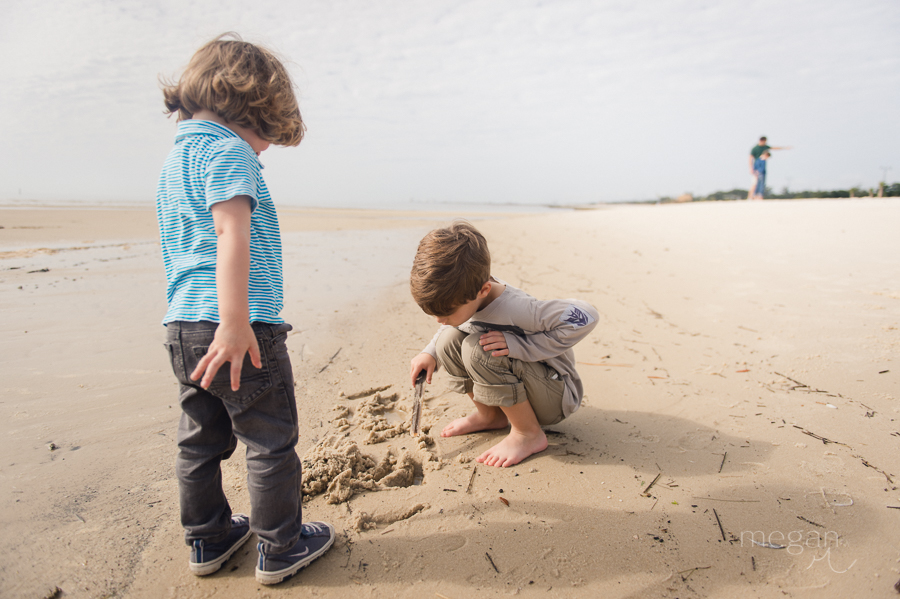photo of two young boys digging in the sand on a beach in natural light