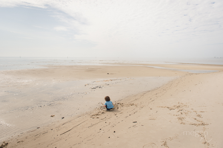 young boy plays in sand under a cloudy sky on the beach