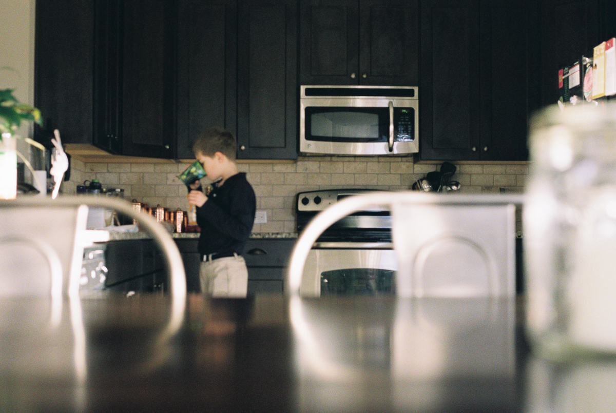 boy in kitchen in out of focus image with foreground framing on fuji 400h film photo shot on nikon fe by megan cieloha photography