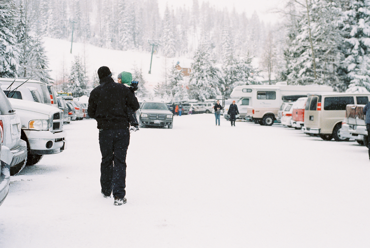 man carries child in snow picture on fuji super 800 film by megan cieloha