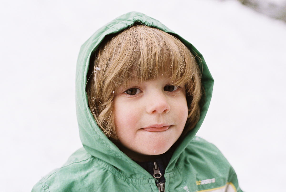 portrait of young boy in snow on fuji super 800 film by megan cieloha