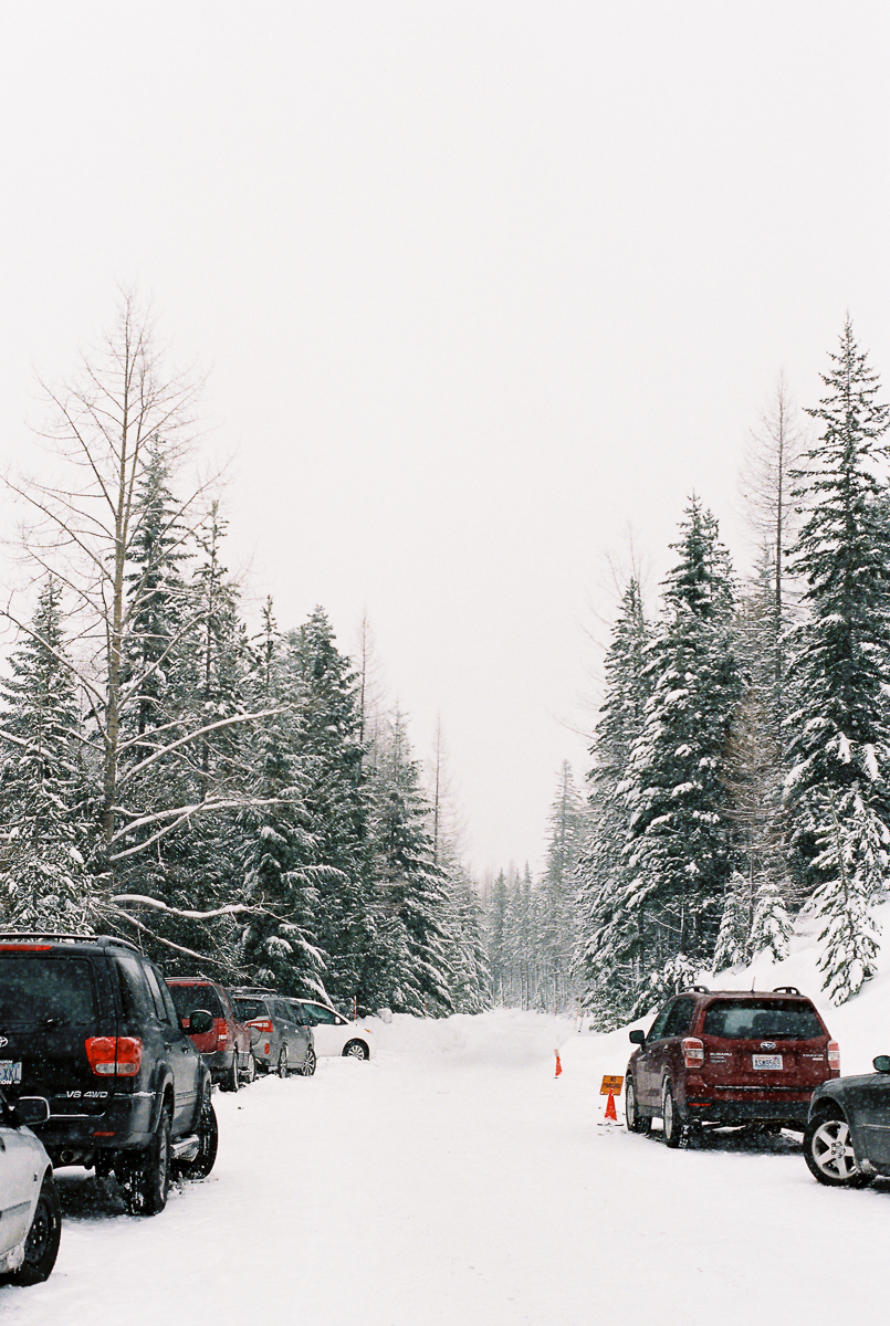cars parked along a road on snowy hill on fuji super 800 film by megan cieloha