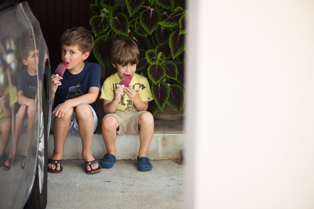 picture of 2 boys eating popsicles together on porch by megan cieloha
