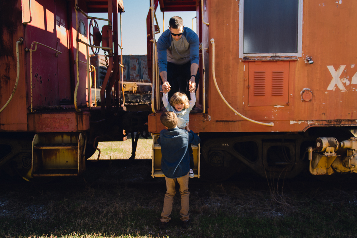 man and boy help toddler down off of train by megan cieloha