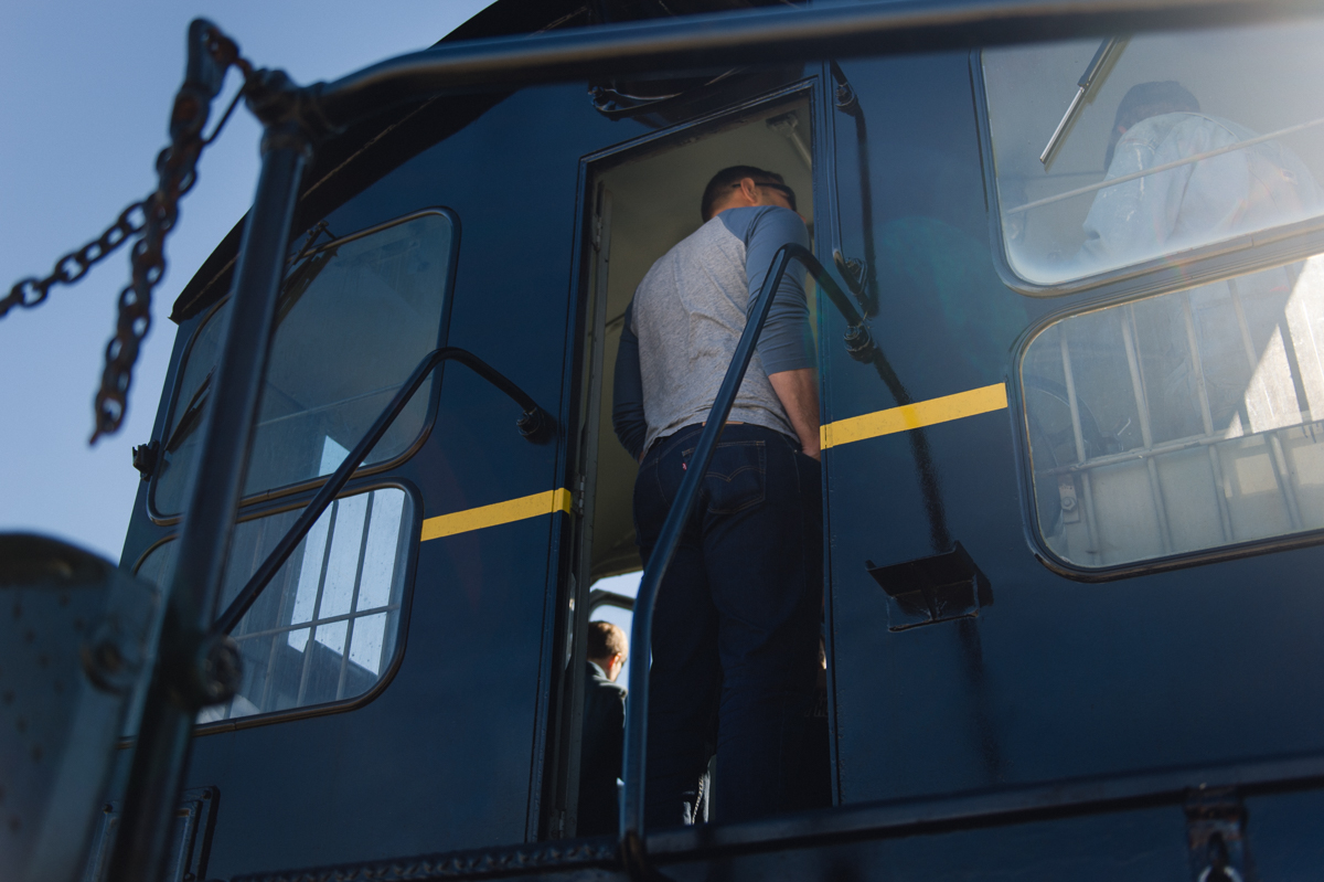 man listens to conductor in a train engine picture by megan cieloha