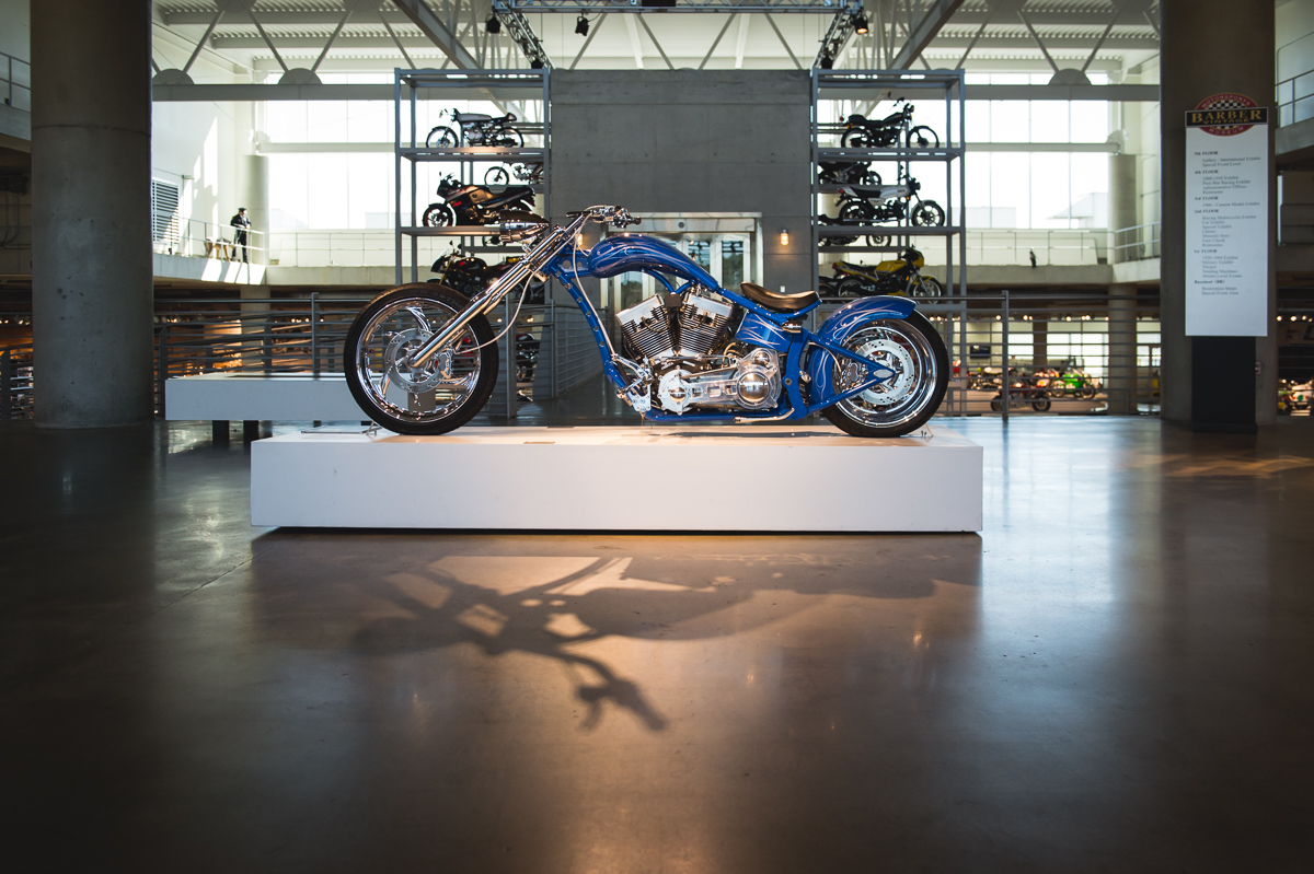 blue motorcycle spotlighted in museum by megan cieloha