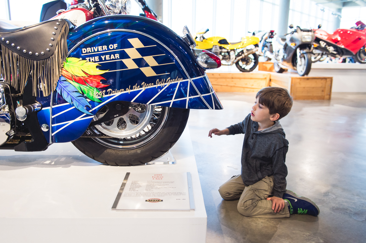 young boy looks at indian motorcycle photo by megan cieloha