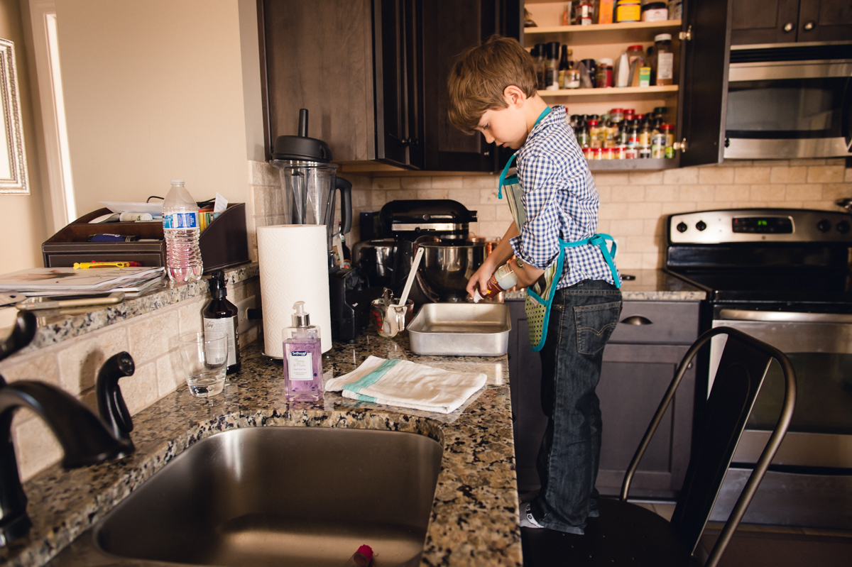 child helps make chocolate chip cookies by megan cieloha
