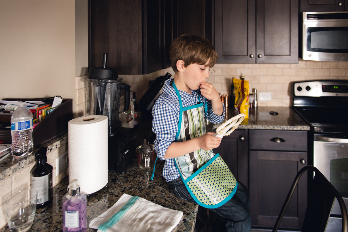 child with mixing beater in kitchen with natural light by megan cieloha