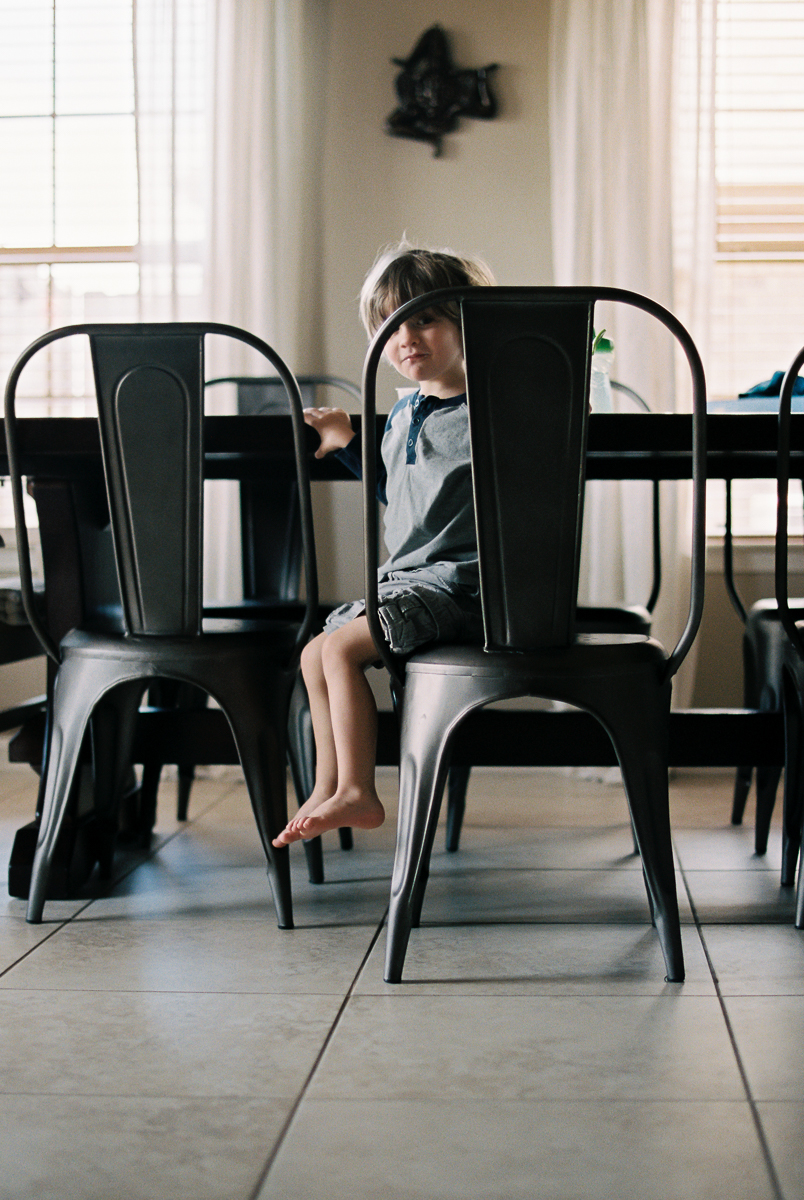 child sits in metal chair at dining room table on portra 400 by megan cieloha