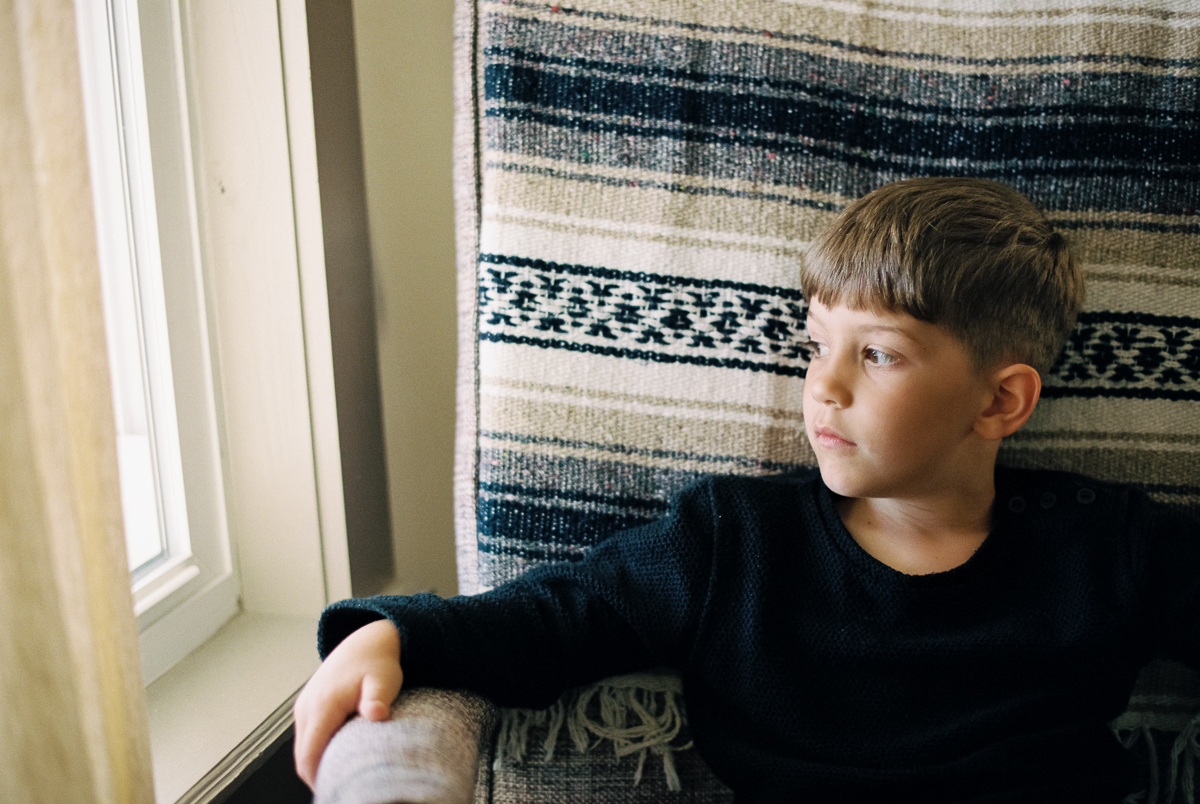 portrait of boy next to window portra 400 film image in natural light photo by megan cieloha