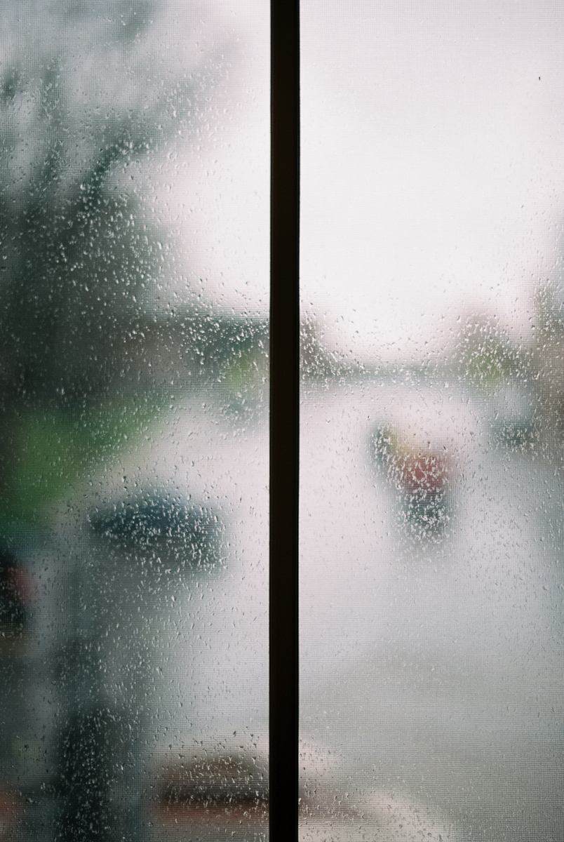 blurry window with rain portra 400 film image in natural light photo by megan cieloha