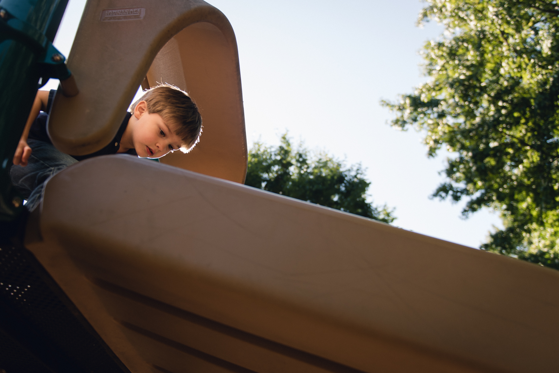 Photo of child at the top of a slide on a playground by megan cieloha