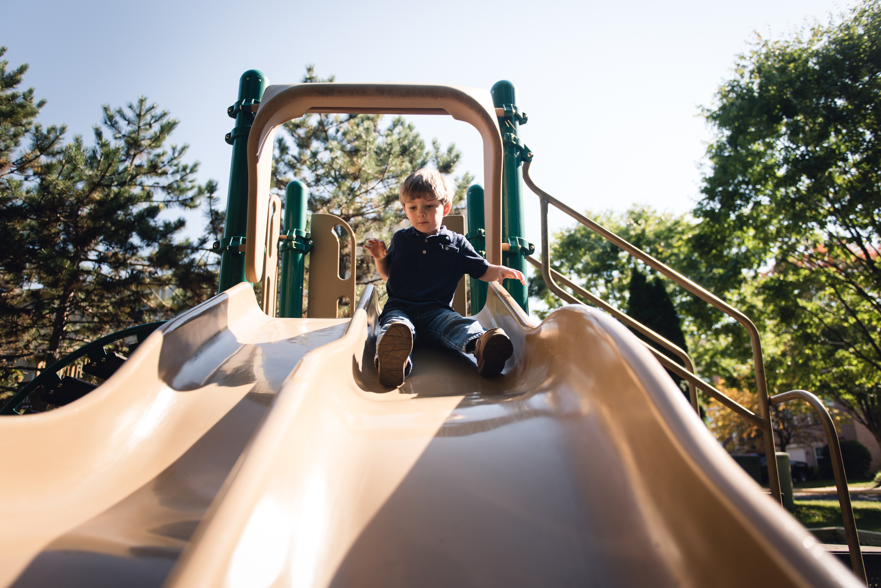 photo of child on slide in full sun by megan cieloha