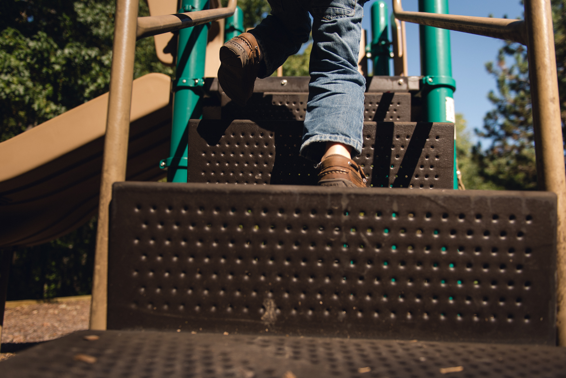 Photo of child climbing stairs in full sun on a playground by megan cieloha