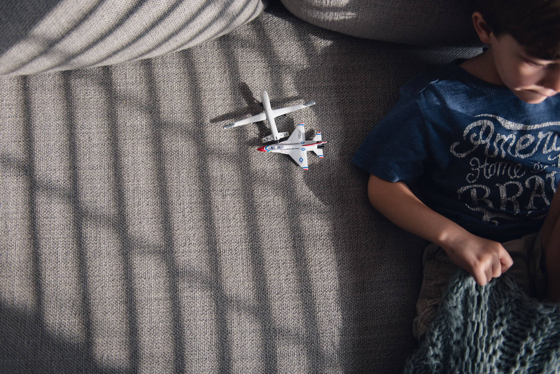 toy planes in natural light next to child on a couch photo by megan cieloha