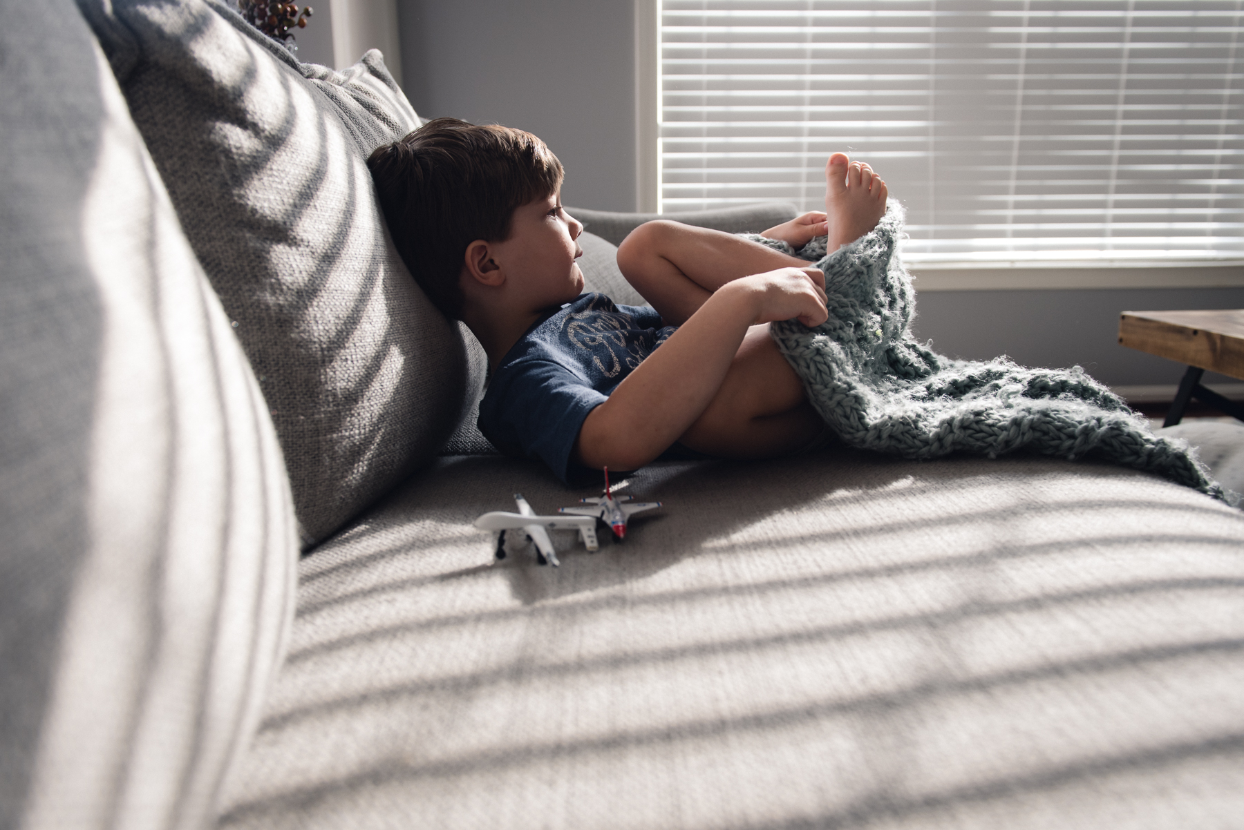 backlit indoor natural light photo of child on a couch by megan cieloha