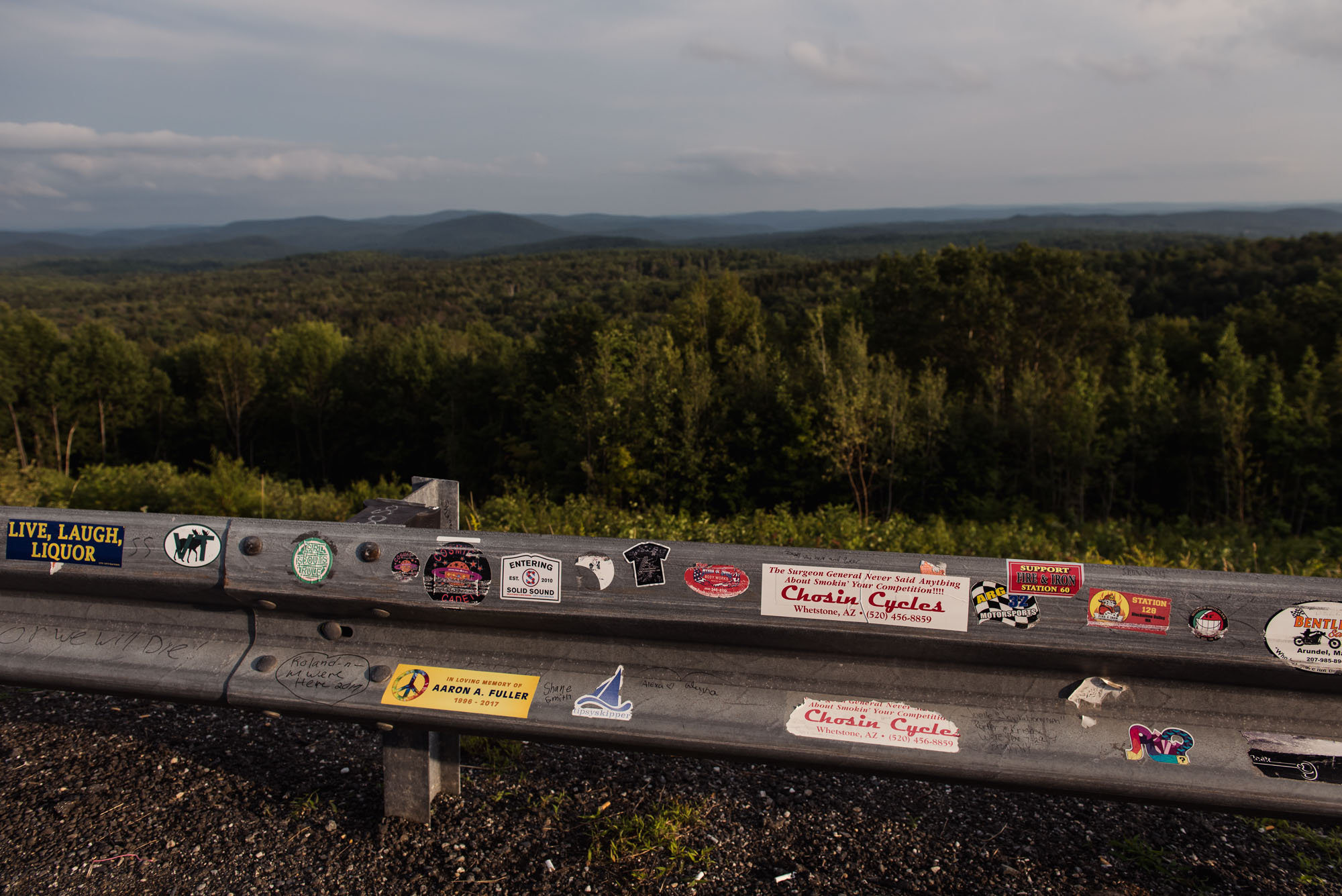 bumper stickers on guard rail in vermont picture by megan cieloha
